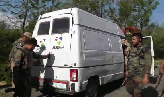 Police and army personnel inspect J&K Bank's cash delivery vehicle after it was attacked by suspected militants in Kulgam's Pombai village on Monday evening. The attack left 5 policemen and 2 bank employees dead.