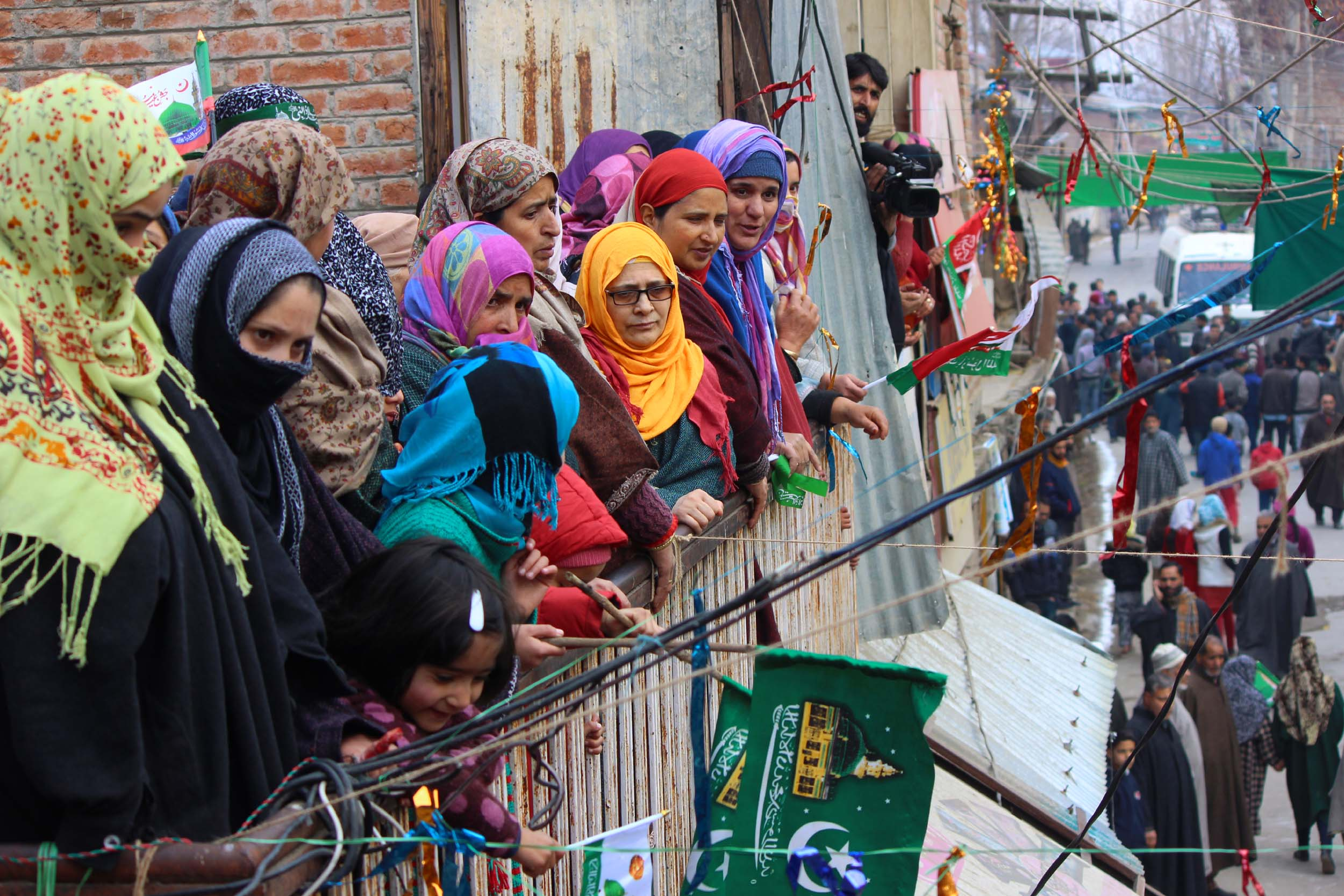 Women watch a milad procession in south Kashmir on Monday.