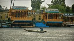 A woman crosses Dal lake amid rains in Srinagar