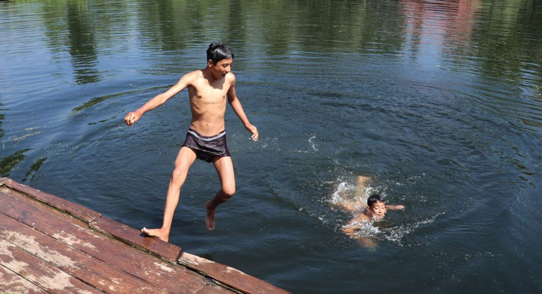 Boys take a dip to beat the heat at Dal Lake in Srinagar