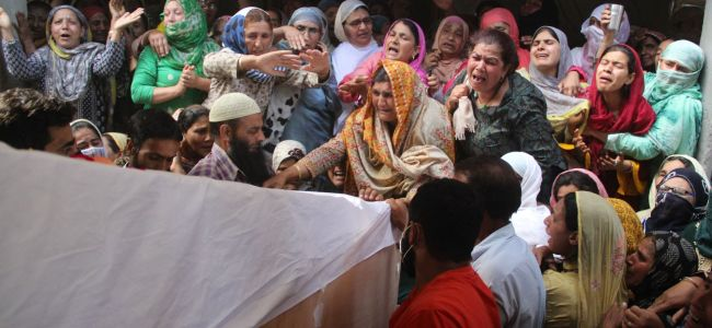Relatives and neighbors lift the coffin of Waseem Ahmed, a policeman who was killed in a shootout, during his funeral on the outskirts of Srinagar