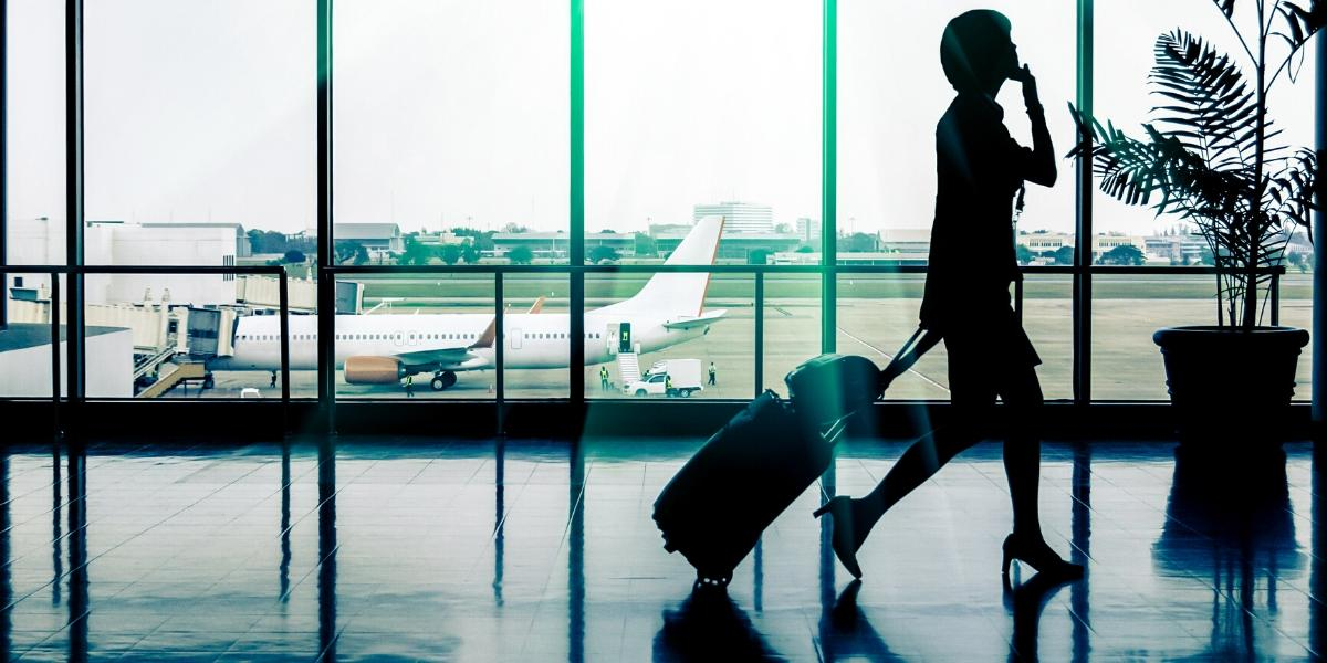 business travel woman in an airport pulling luggage