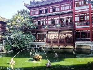 green pond with a fountain in front of a chinese style building
