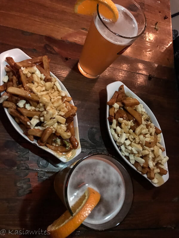 two plates of poutine and a glass of beer is all you need to fall in love with montreal