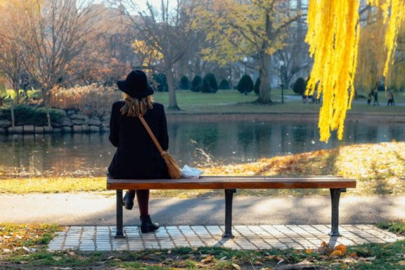 a woman sitting on a bench in a park with leaves falling