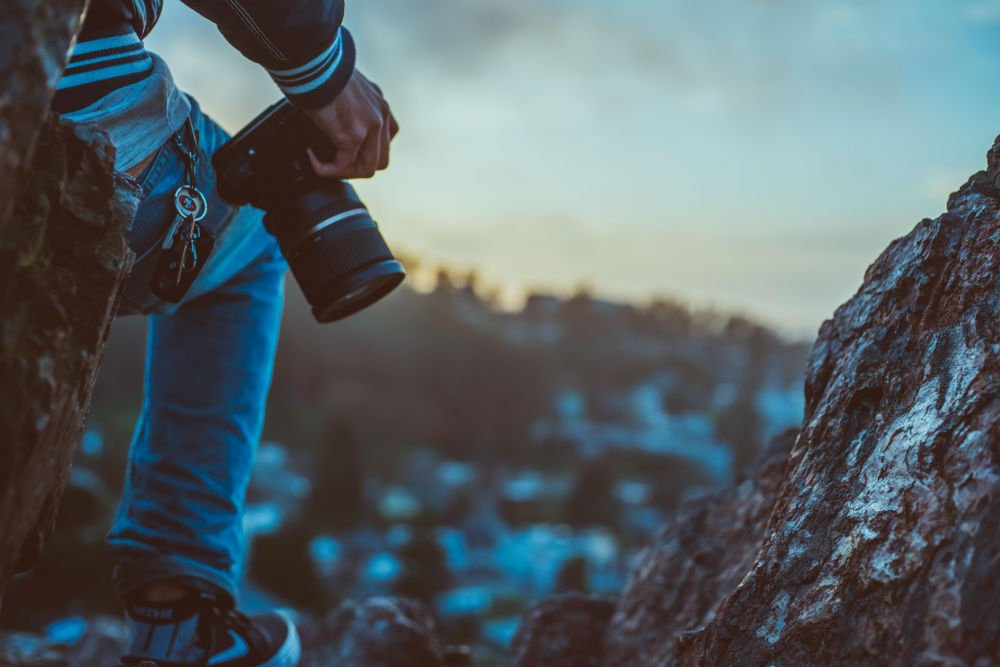 photographer holding a camera on a mountain