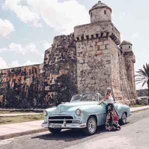 woman leaning against vintage old blue car with a stone tower in the background