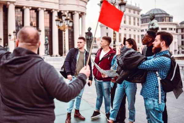man with red flag leading a group of tourists