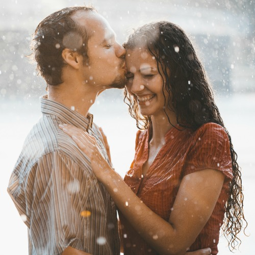 cople in love hugging and kissing under summer rain