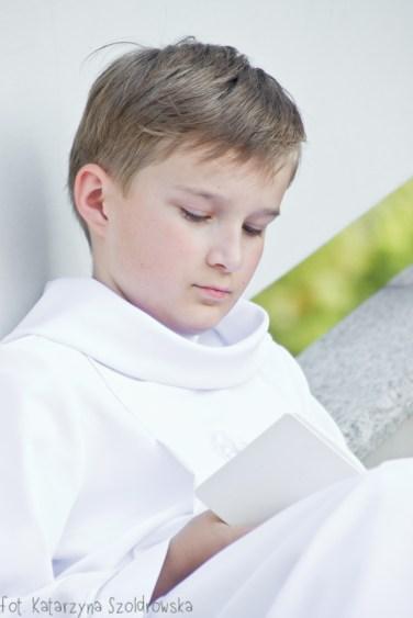 Sesja komunijna wykonanaprzed kościołem św. MaksymilianaMariiKolbego,parafia Mistrzejowice. Chłopiec siedzi przed kościołem i modli się z modlitewnikiem w dłoni