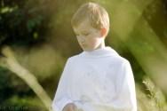 Portret komunijny.Plenerowa sesja zdjęciowa z okazji pierwszej komuni świętej. Zdjęcie przedstawia chłopca ubranego na biało wsród traw. Zdjecie wykonał fotograf dziecięcy w Krakowie, Nowa Huta Mistrzejowice