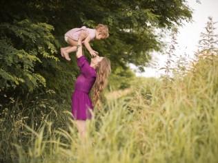 Sesja mamy z dzieckiem. Młoda kobieta bawi się z córeczką wśród pól w Krakowie.Sesja dziecięca w plenerze w Krakowie Mistrzejowice