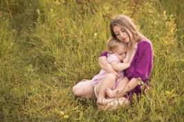 Sesja zdjęciowa matki z dzieckiem przy piersi. młoda matka karmiąca 2 letnie dziecko wśród traw. Sesja rodzinna matka i dziecko wykonana przez fotografa dziecięcego w Krakowie, Nowej Hucie. Karmienie piersią sesja fotograficzna