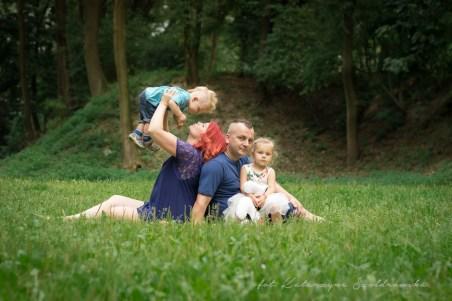 Fotografia rodzinna i dziecięca w Krakowie. Sesja rodzinna w plenerze. Rodzina z dwójką dzieci pozuje na trawie. Matka podnosi rocznego chłopczyka do góry. Sesja rodzinna w Mistrzejowicach, Nowa Huta