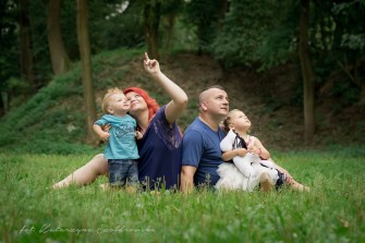 Plenerowa sesja rodzinna na osiedlu Złotego Wieku, Nowa Huta w Krakowie. Rodzice z dwójką dzieci siedzą na trawie. Mama pokazuje rocznemu chłopczykowi lecący samolot .