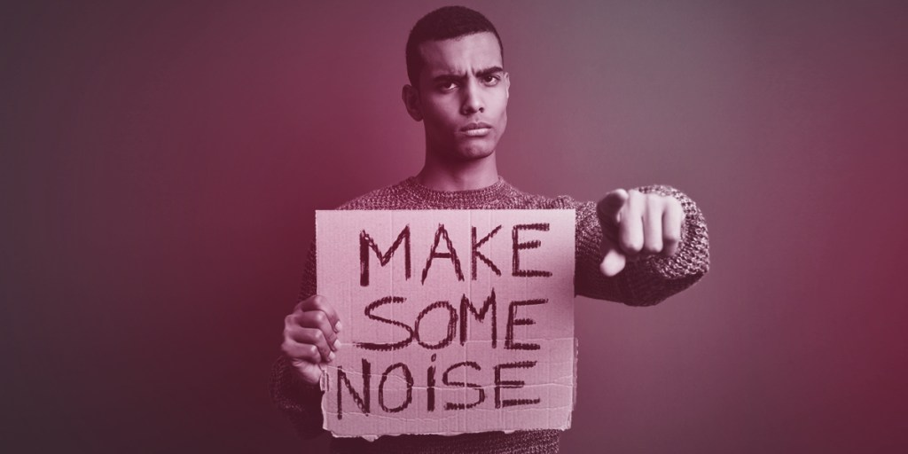 Man with 'Make Some Noise' sign (Crisis Communications)