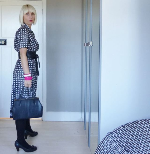 Vintage monochrome black and white fashion dress as worn by Kate Beavis Vintage Home including Clarks Shoes, Tesco F+F coat, Miss Selfridge obi belt and vintage accessories