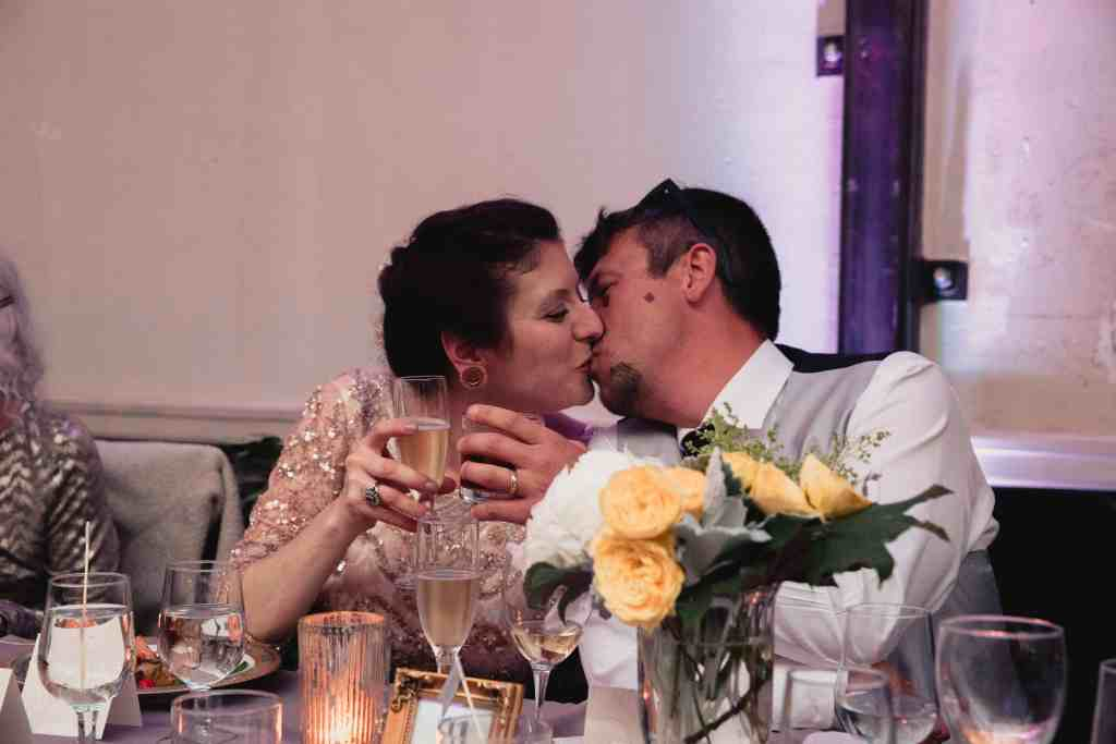 bride and groom kissing during speeches at unique wedding venue