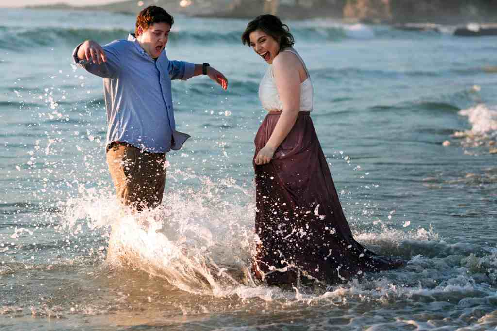 couple getting caught in the waves