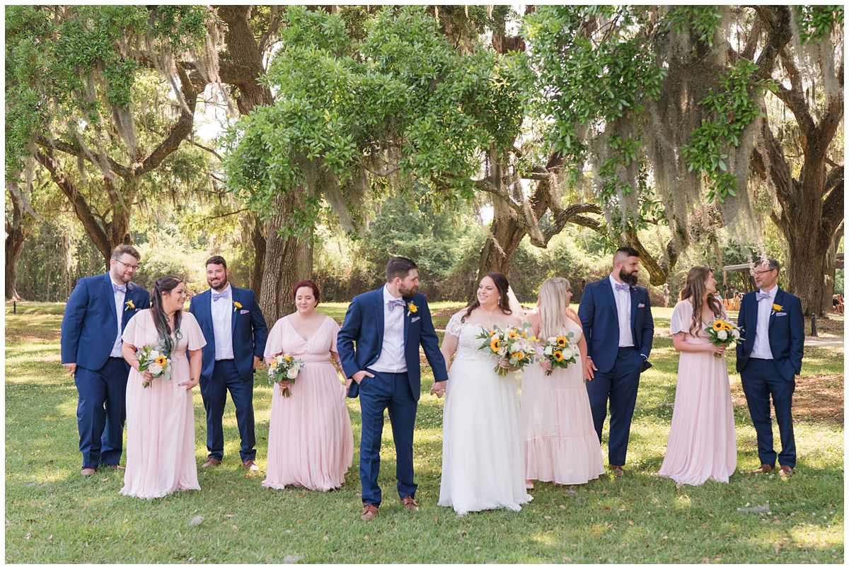 bride and groom walk with bridal party outside Boone Hall