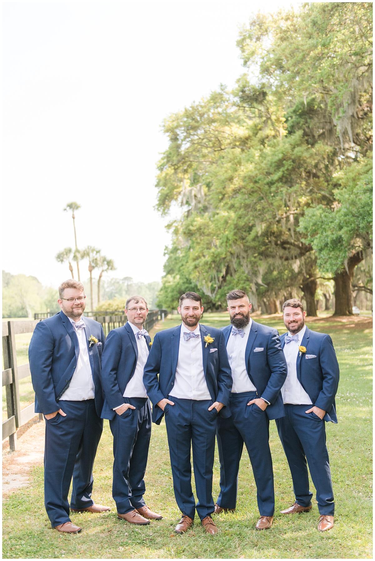 groom poses with groomsmen in navy suits