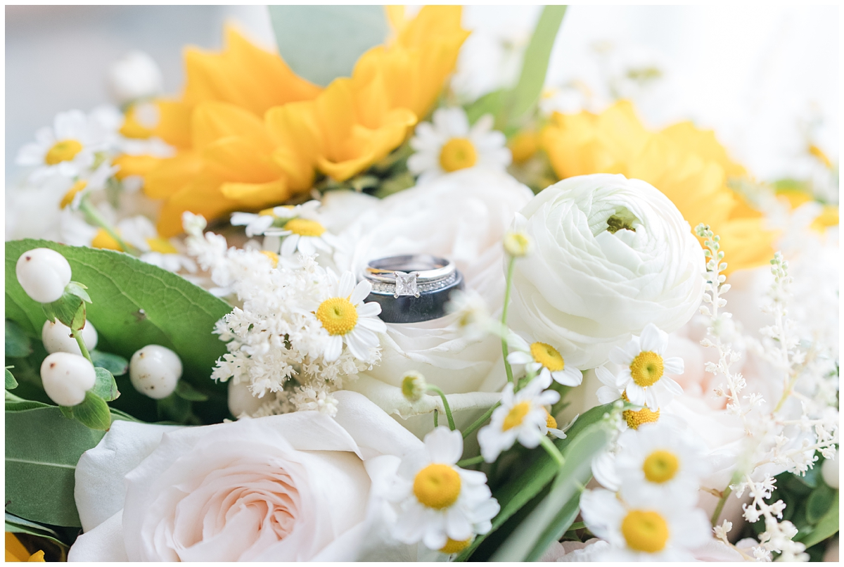 wedding bands sit on yellow and pink flowers