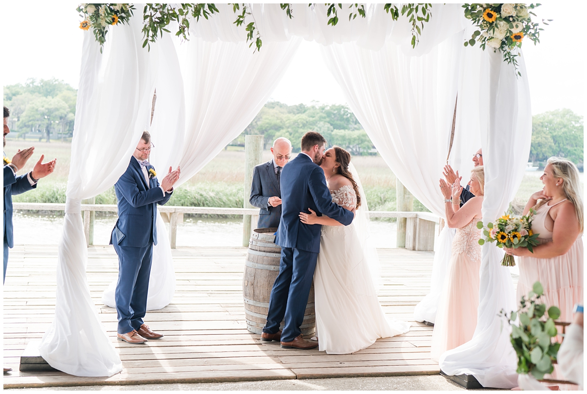 newlyweds kiss under canopy on Cotton Dock in South Carolina
