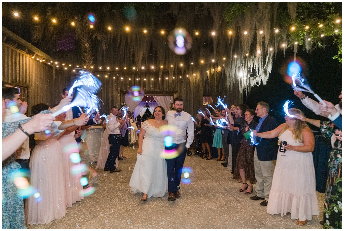 bride and groom leave reception with glow stick exit