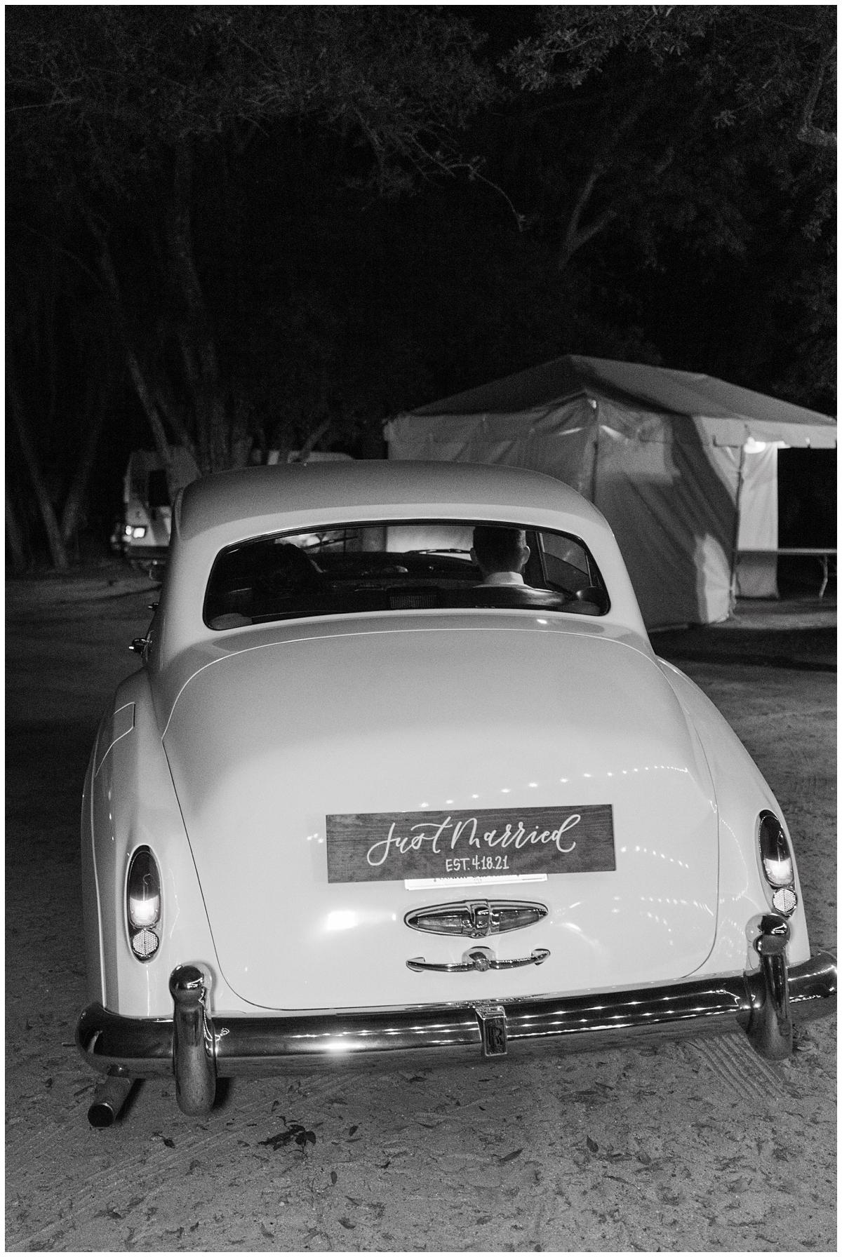 newlyweds leave wedding reception in classic car