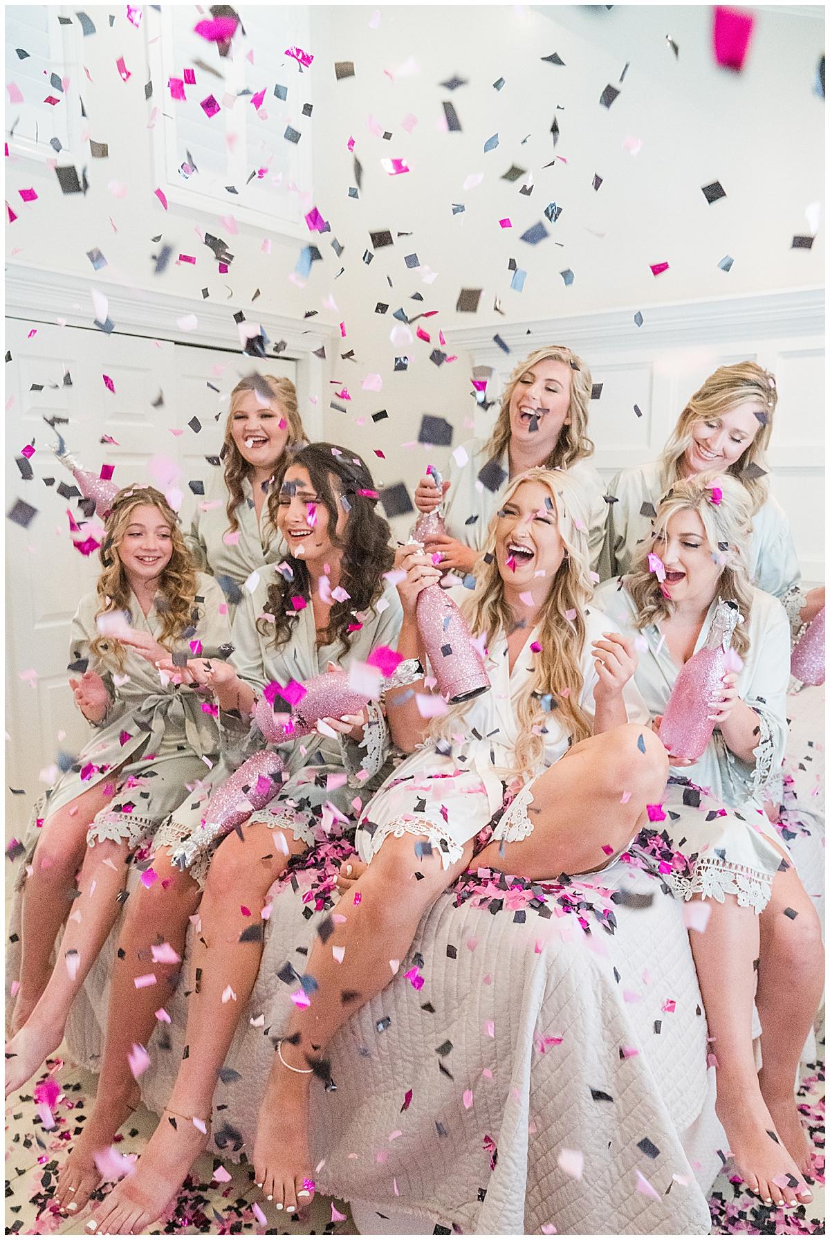 bride and bridesamids pop confetti during wedding day prep