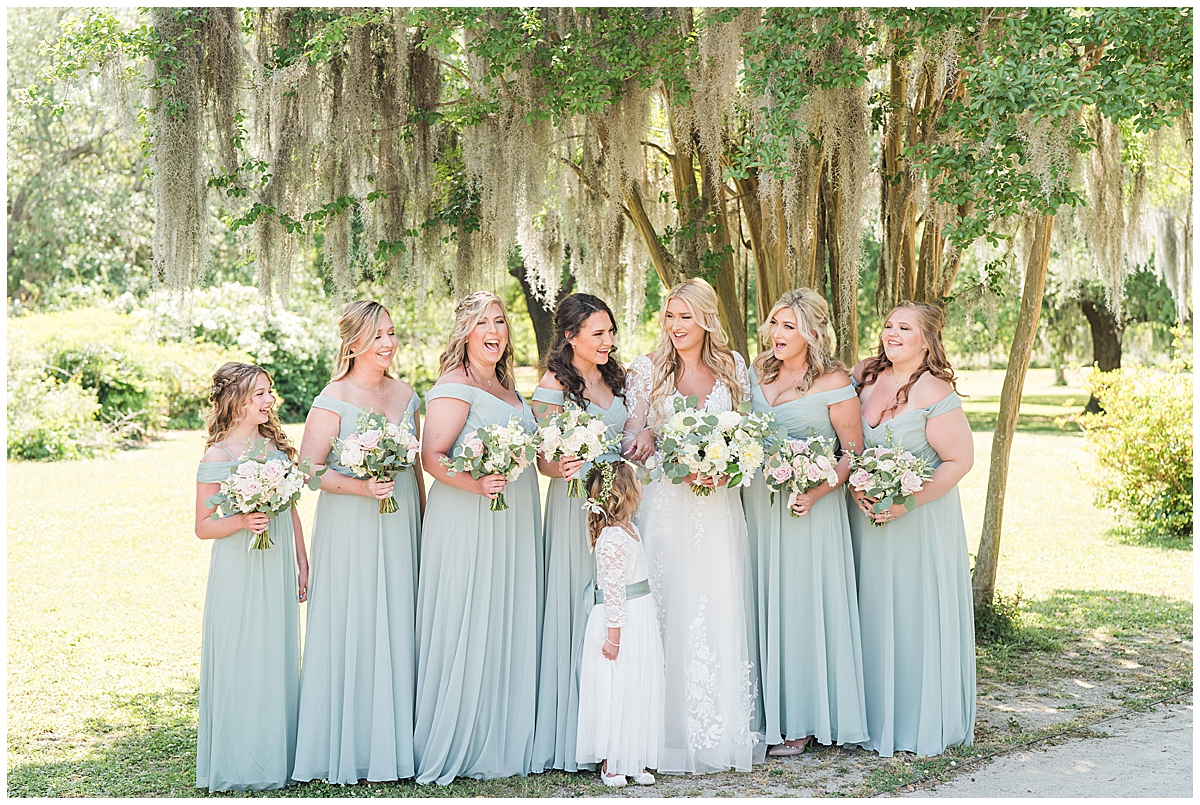 bride poses with bridesmaids in pale green otufits