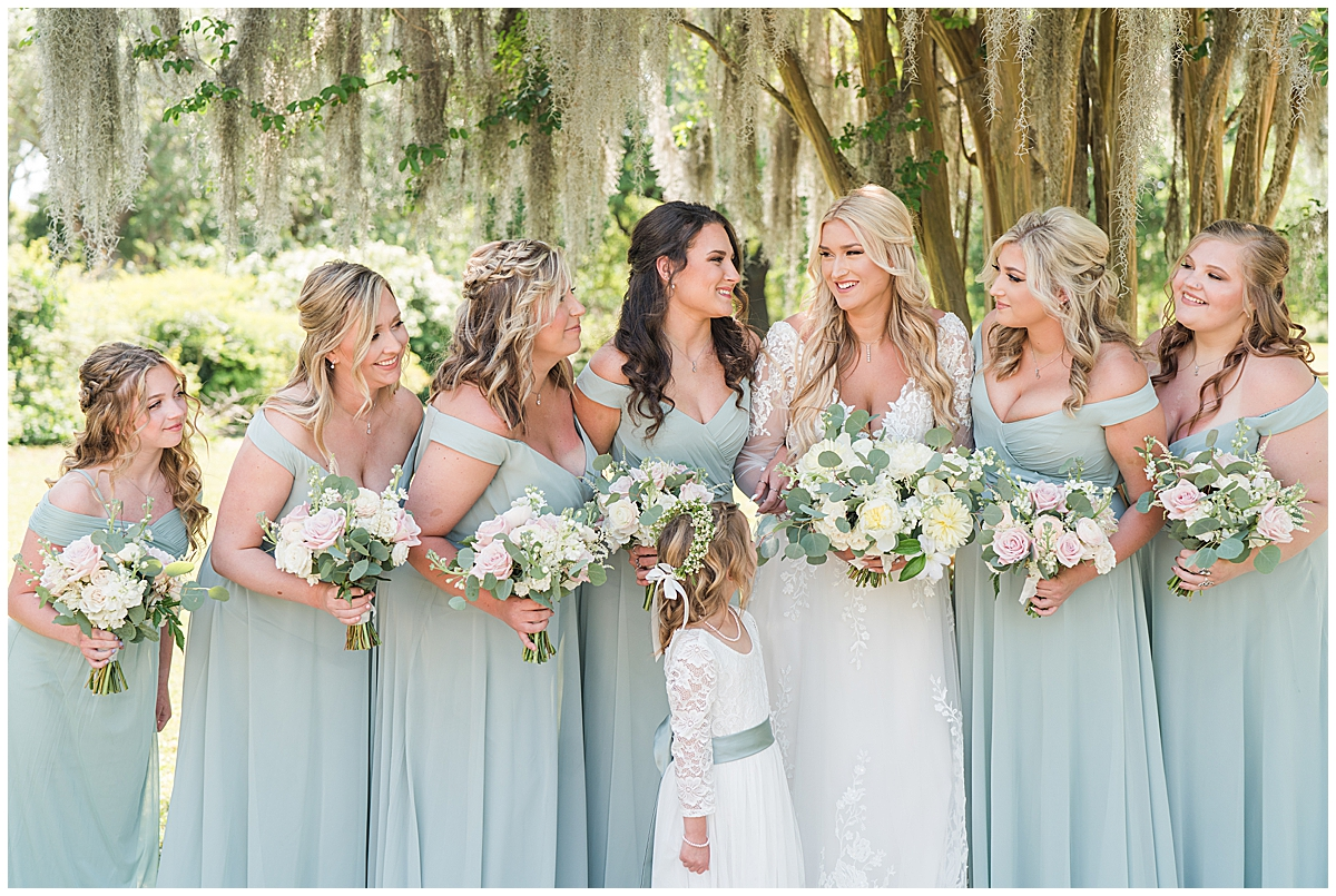 bridesmaids hold yellow and ivory flowers in light green dresses