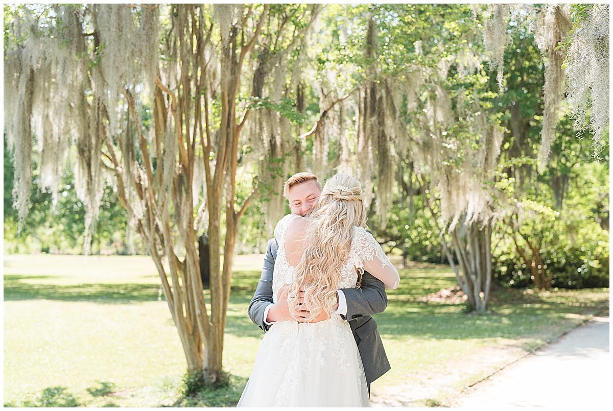 bride and groom hug during first look in Charleston SC