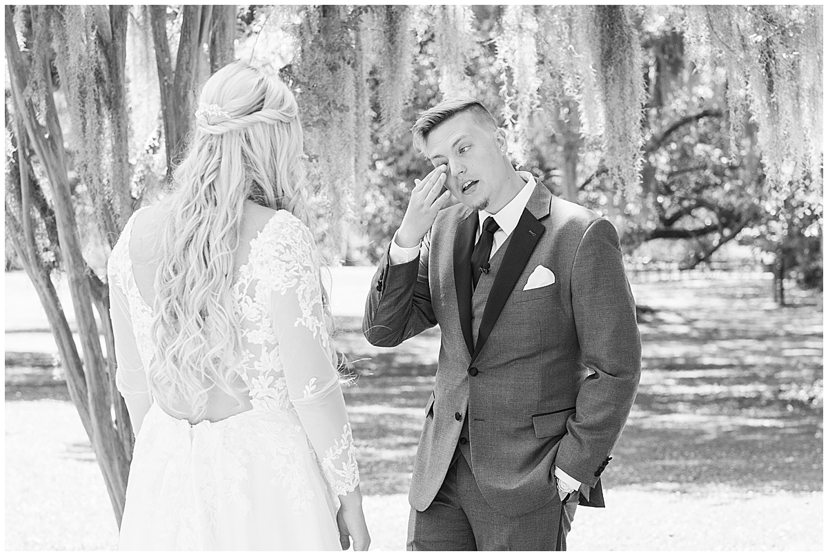 groom wipes tear away during first look before Cannon Green wedding