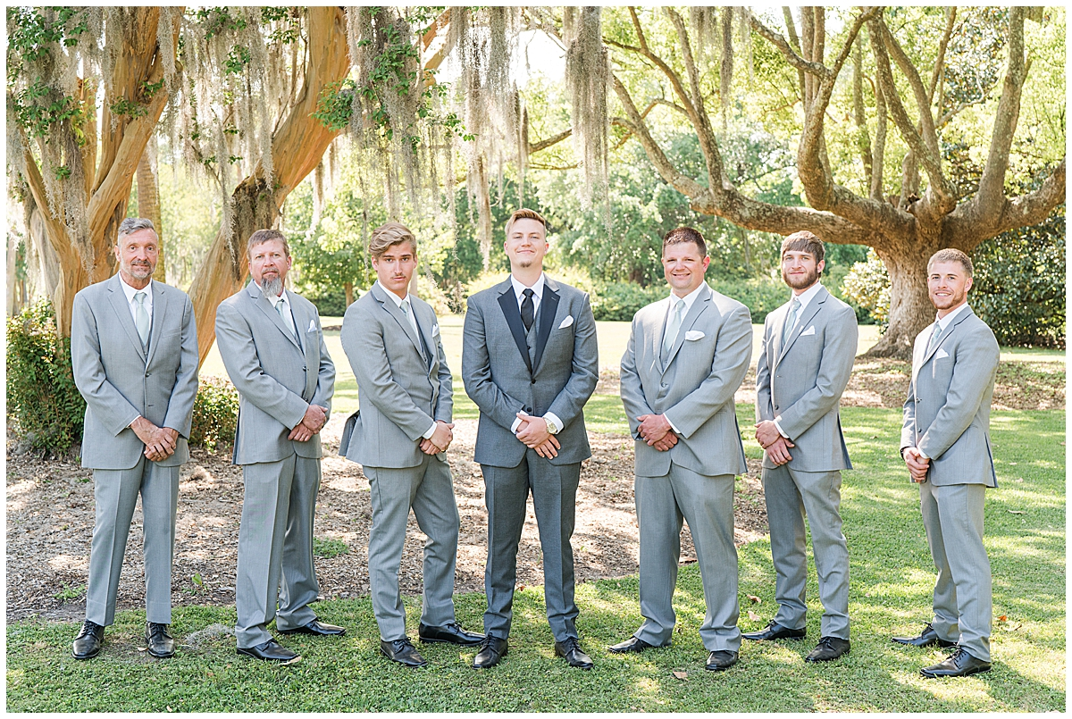 groom and groomsmen in grey suits pose before Cannon Green wedding