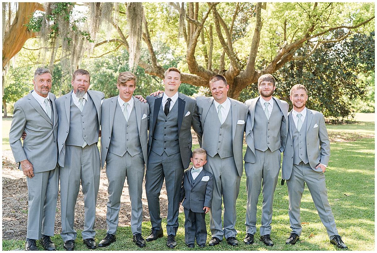 groom poses with groomsmen in grey suits