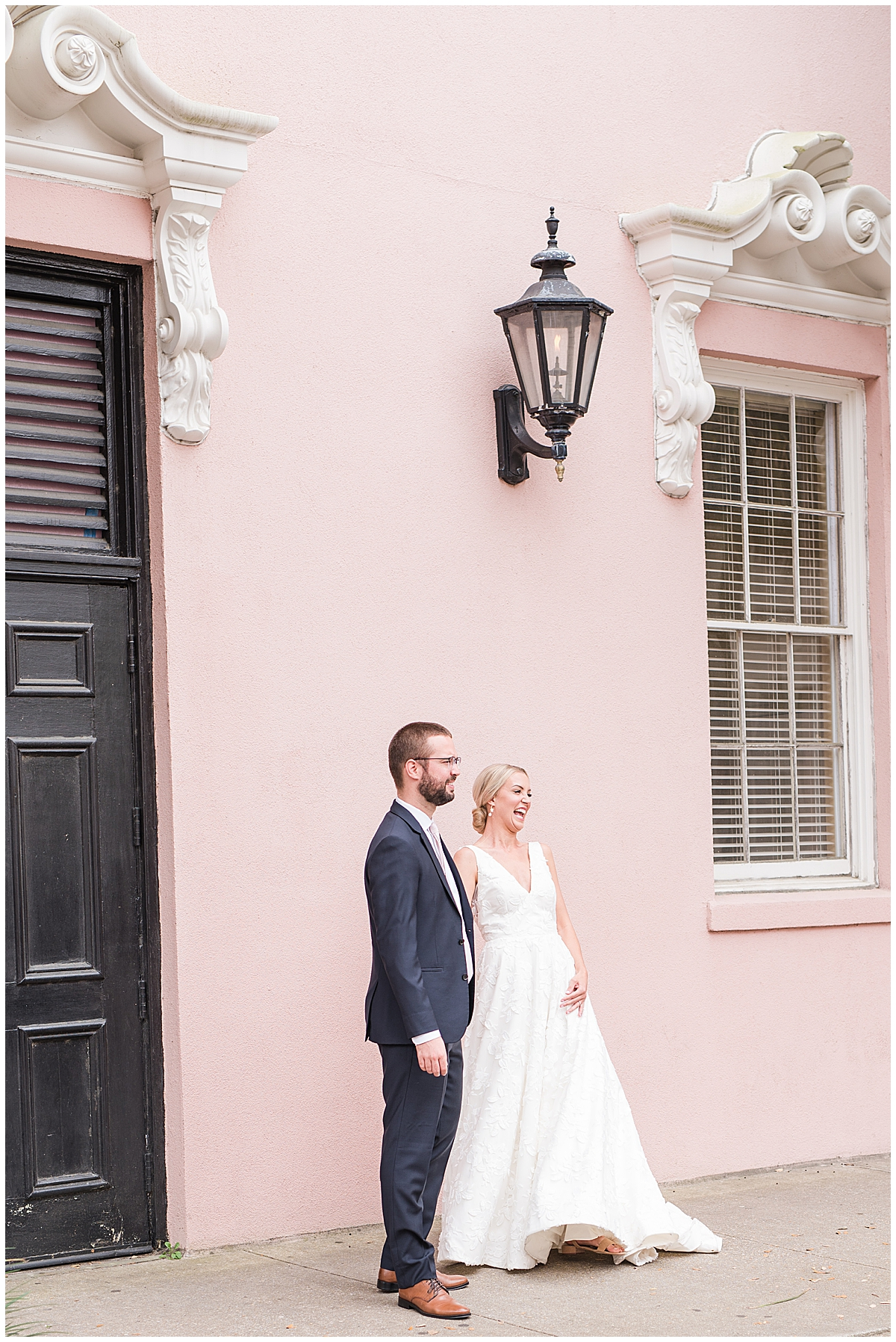 bride and groom laugh standing along Rainbow Row