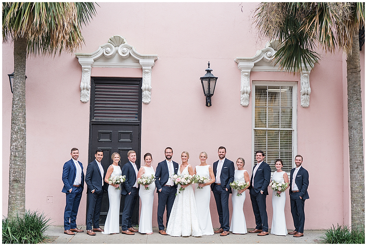 bride and groom pose with bridal party in white dresses and navy suits