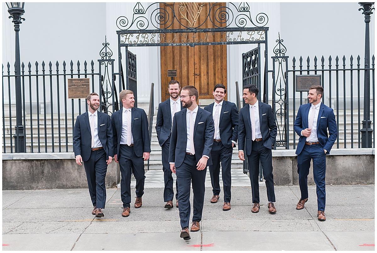 groom walks with groomsmen outside wrought iron gate