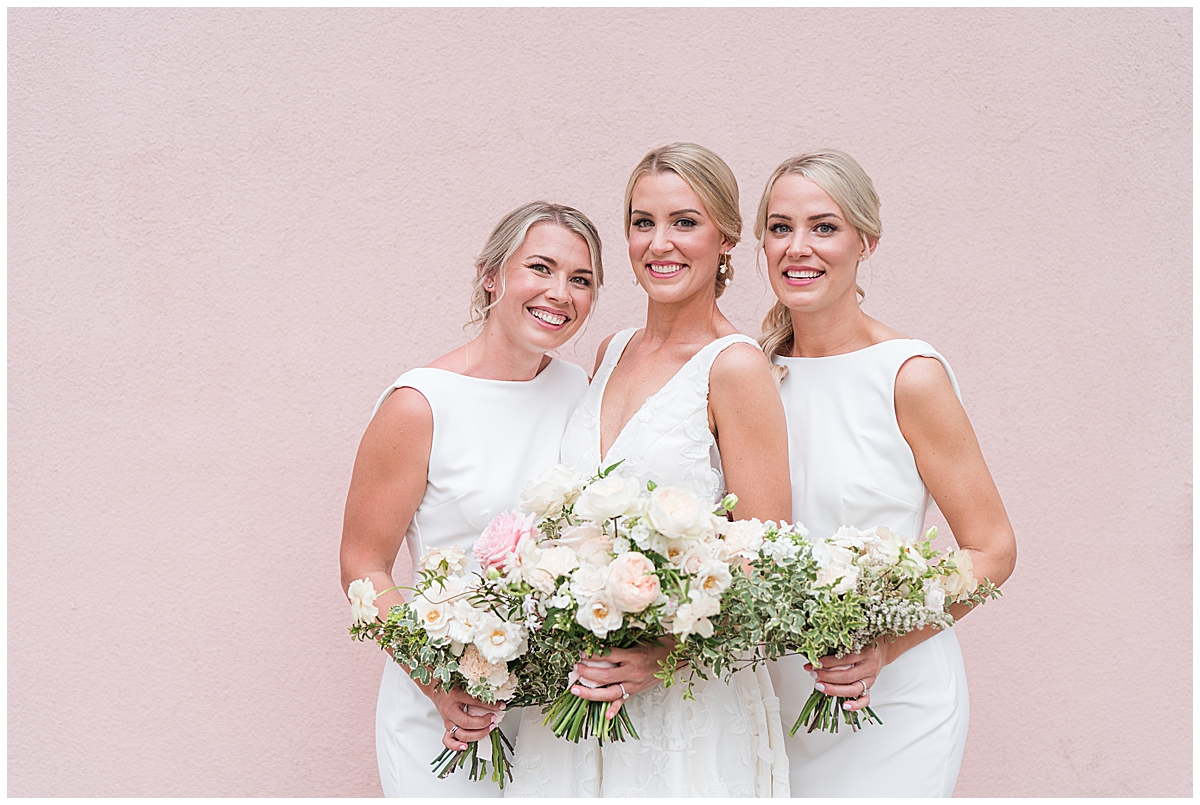 bride hugs sisters along pink wall