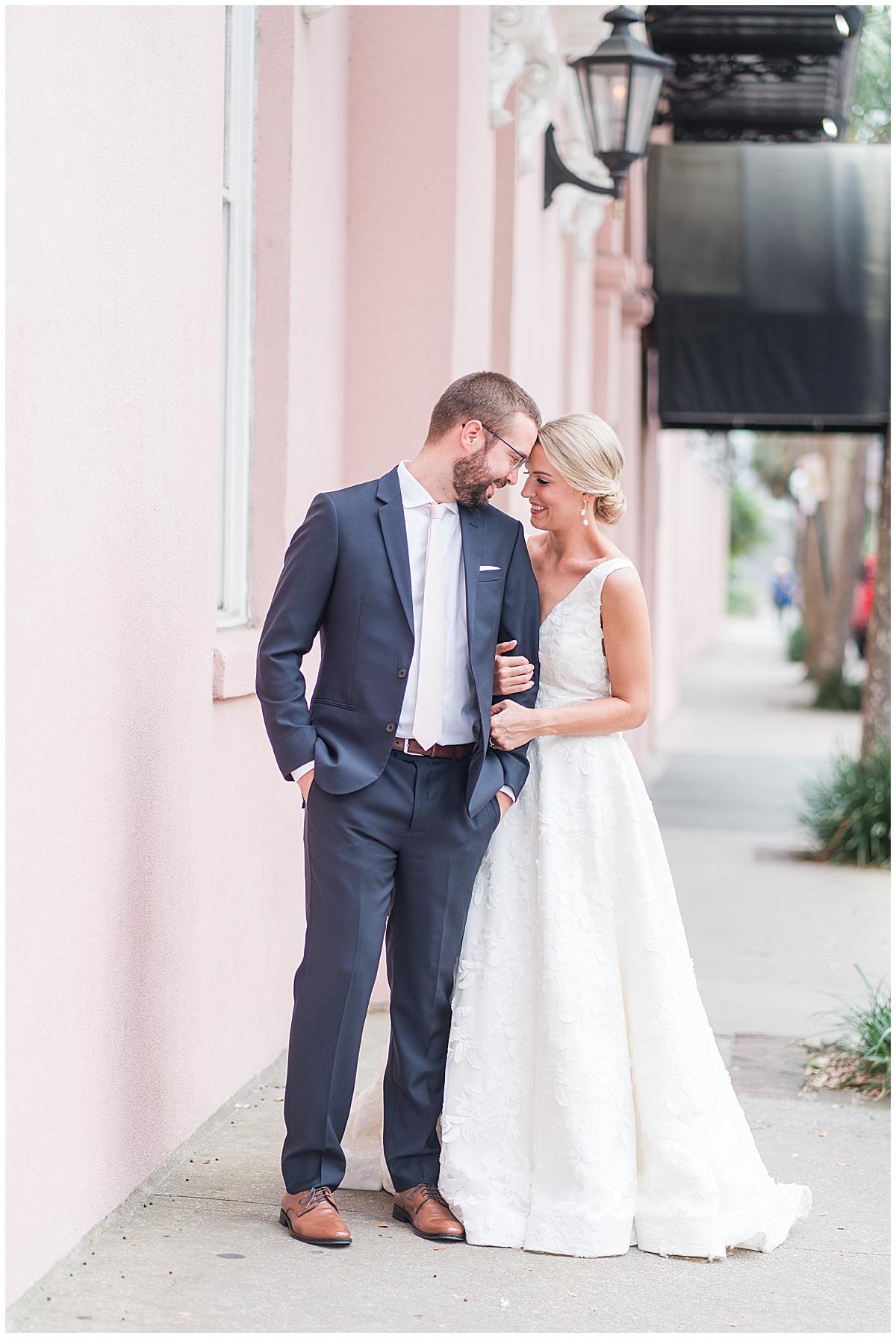 bride and groom pose on Charleston sidewalk