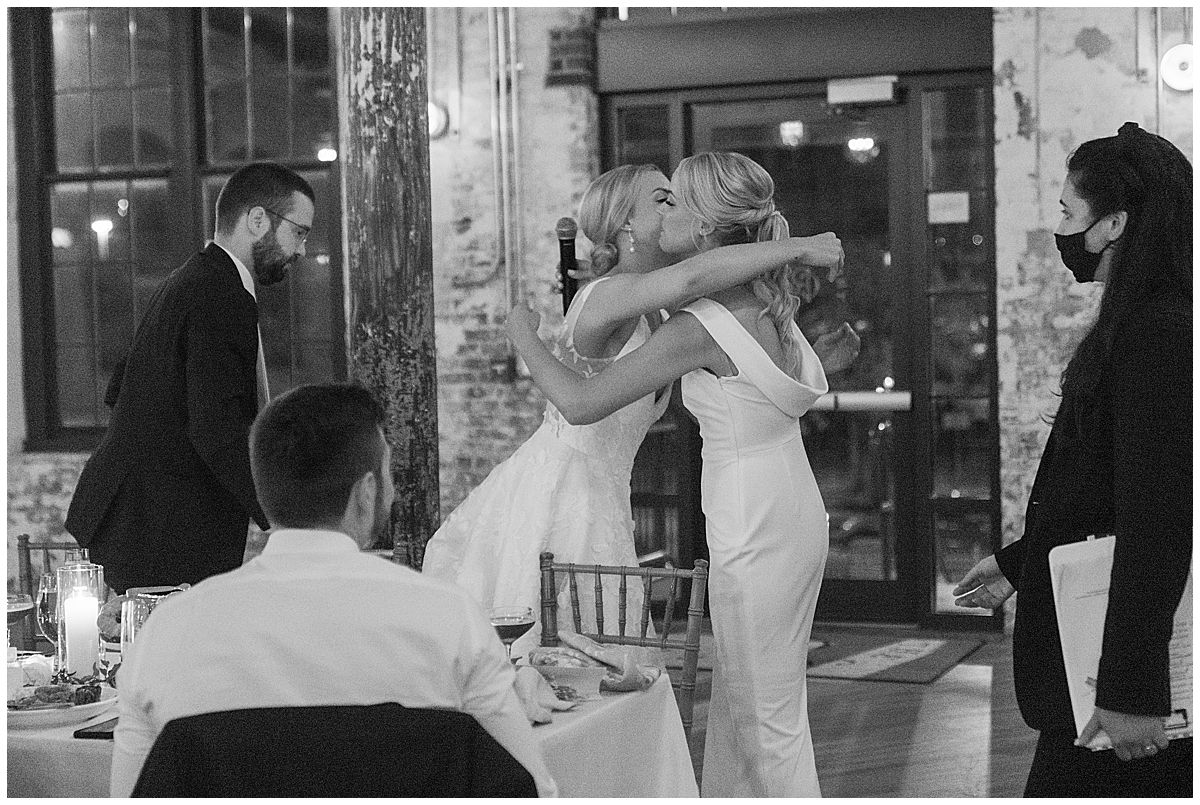 bride kisses maid of honor during toasts
