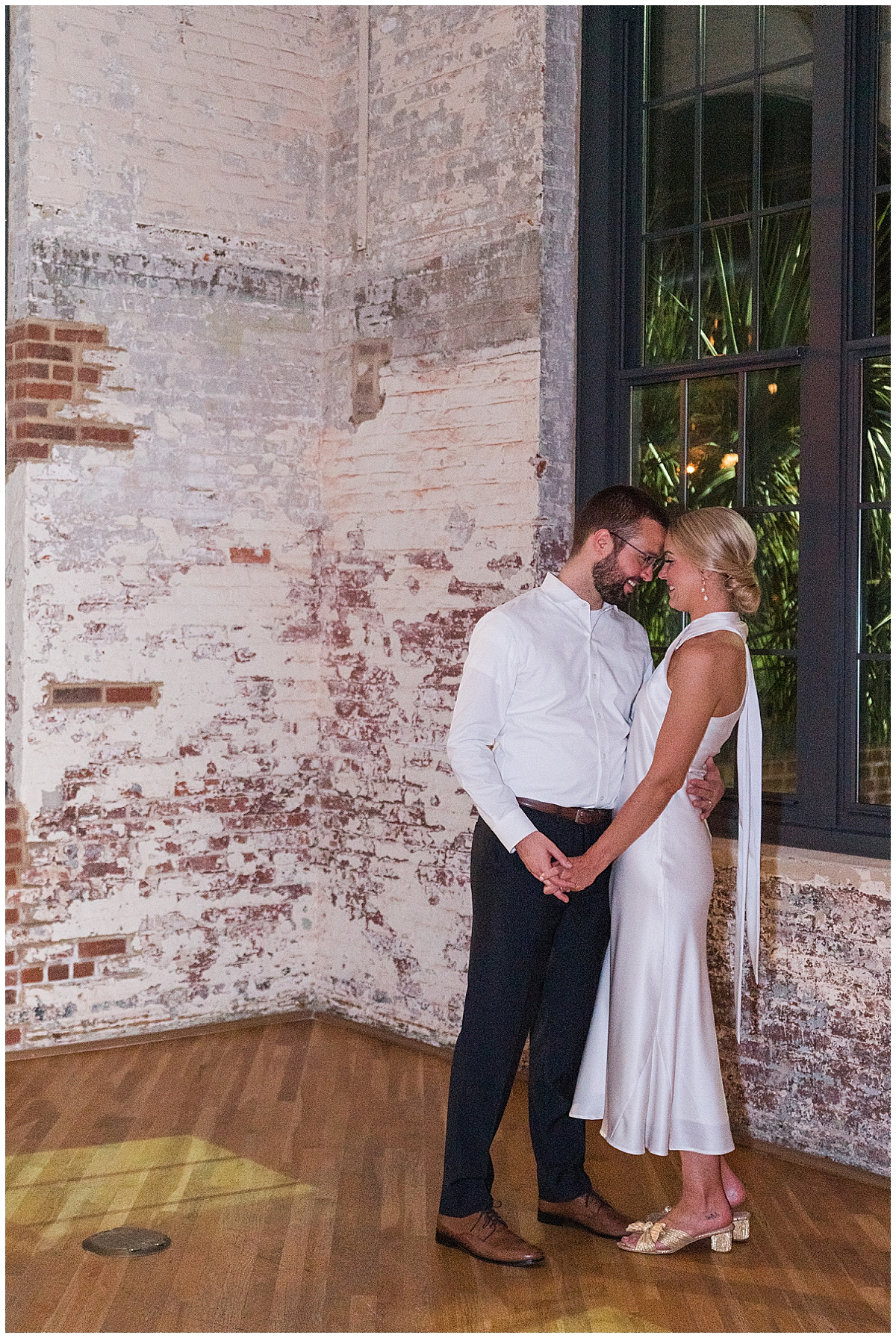 bride and groom pose by brick wall in Cedar Room