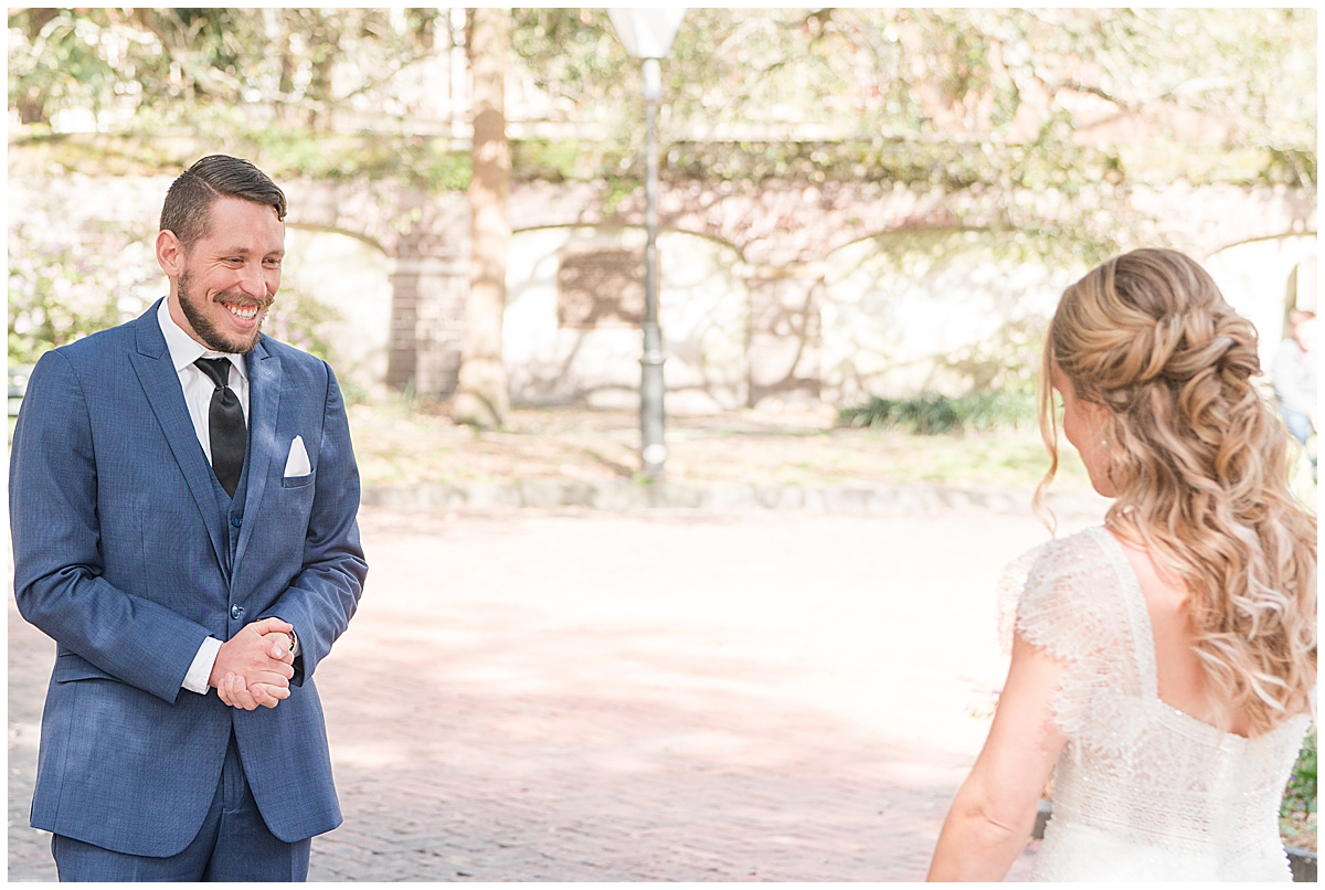 groom in blue suit sees bride for the first time during first look