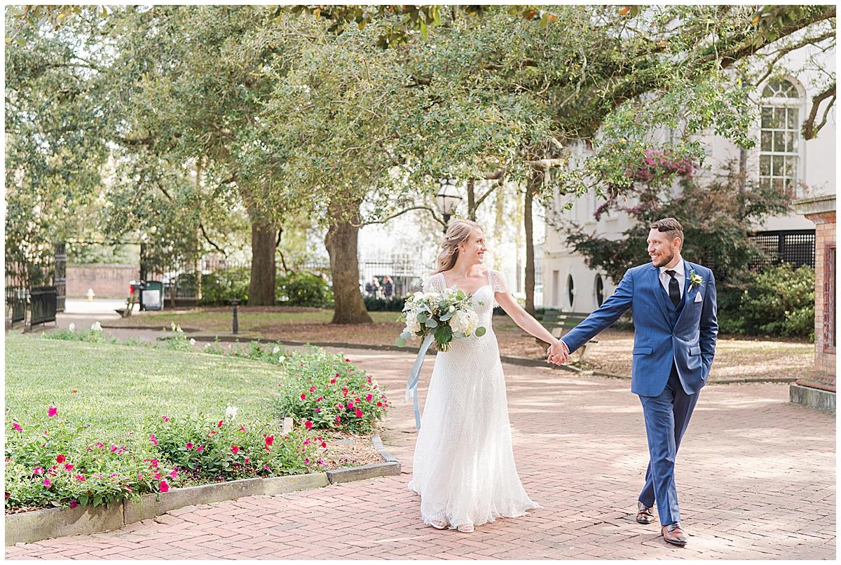 bride and groom hold hands walking through Charleston park