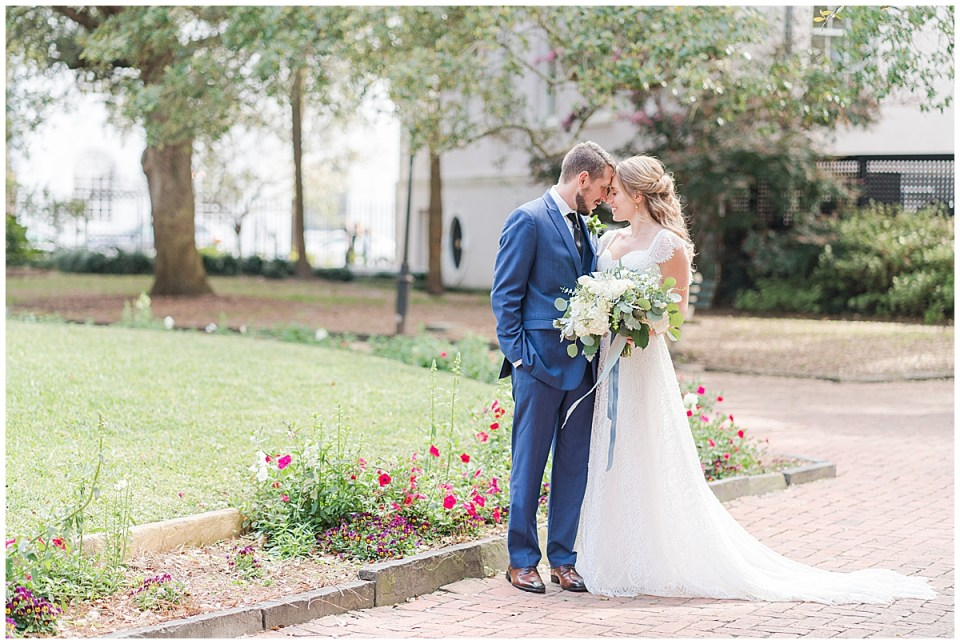 bride and groom pose with noses touching in Charleston park