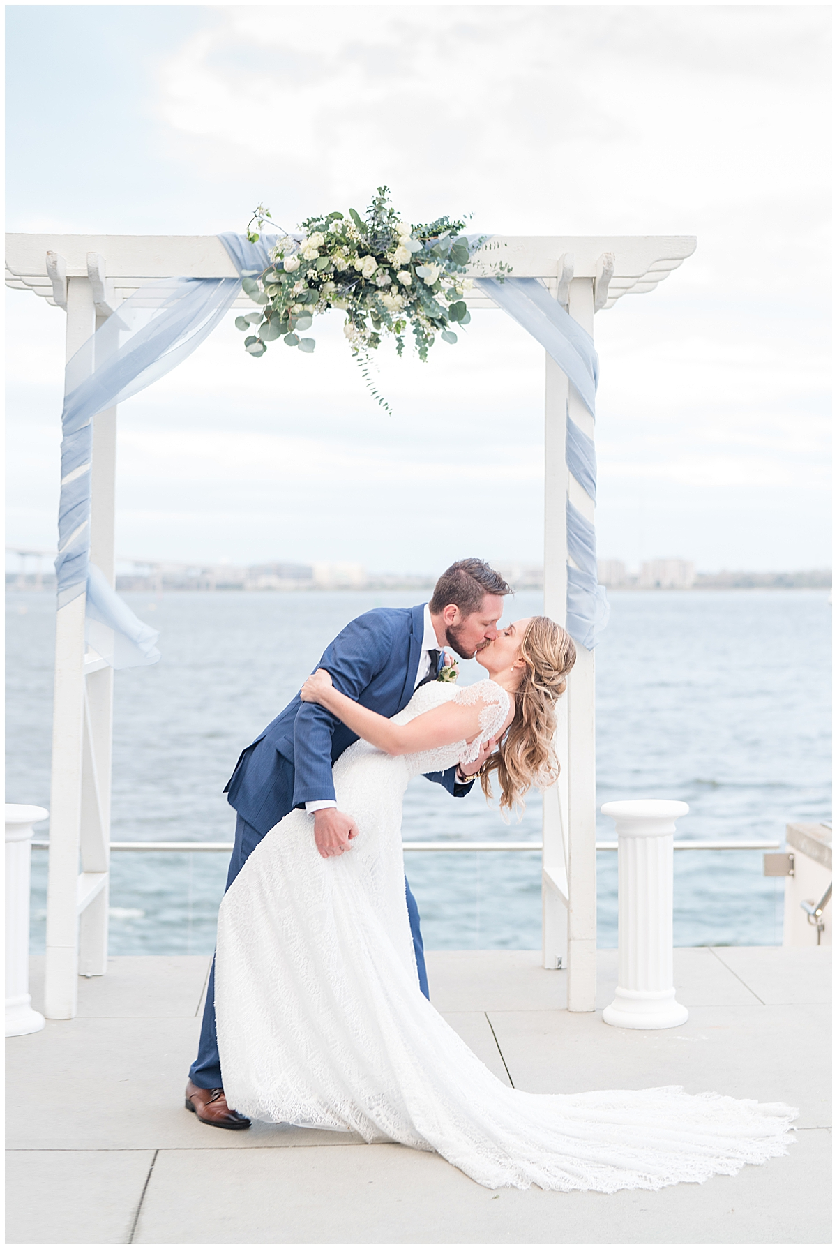 groom dips bride during kiss in front of arbor with blue ribbon