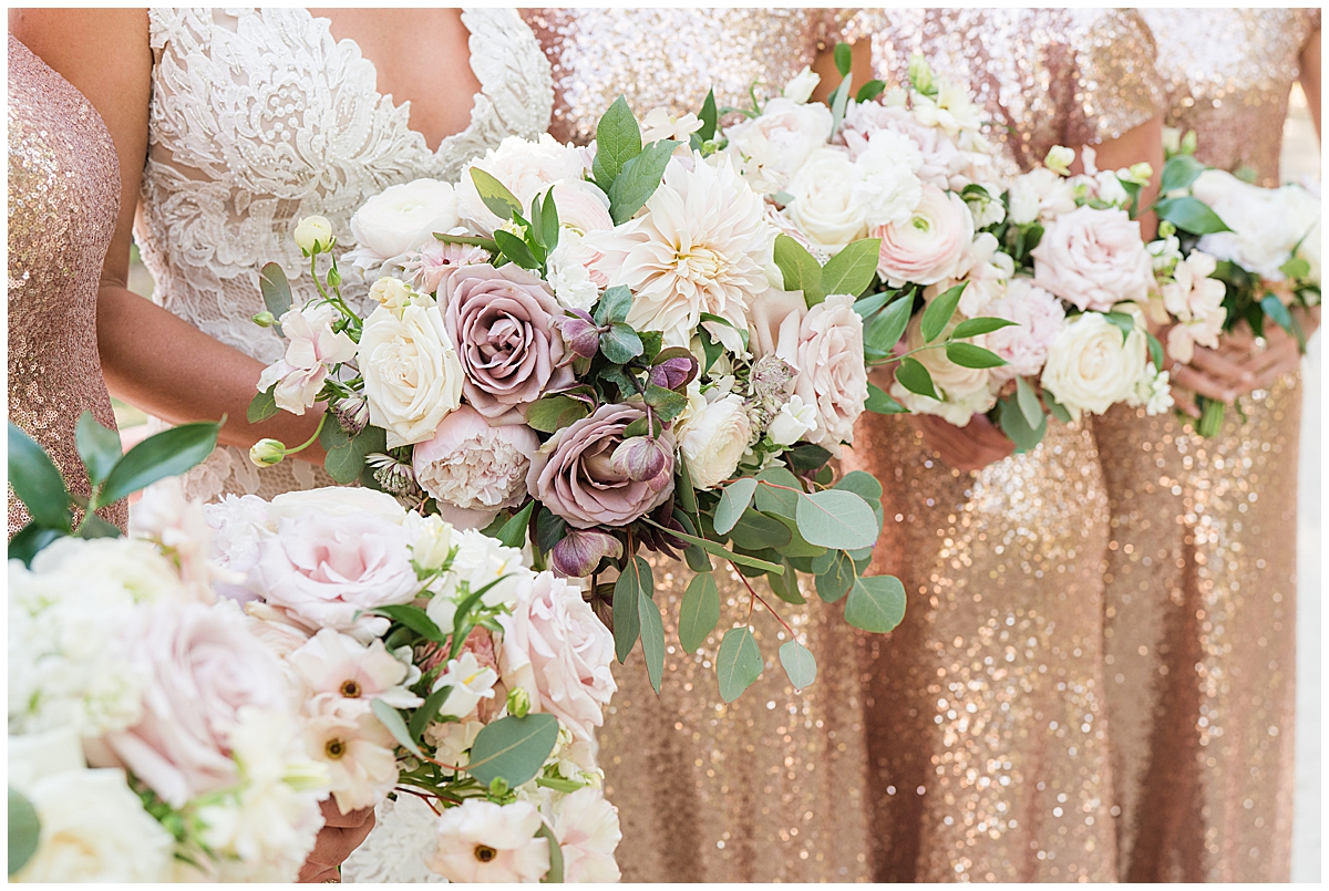 bridesmaids wearing rose gold dresses hold bouquets with ivory and mauve flowers