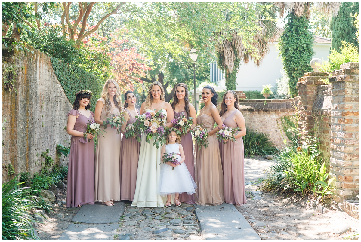 bride and bridesmaids pose together on Charleston street