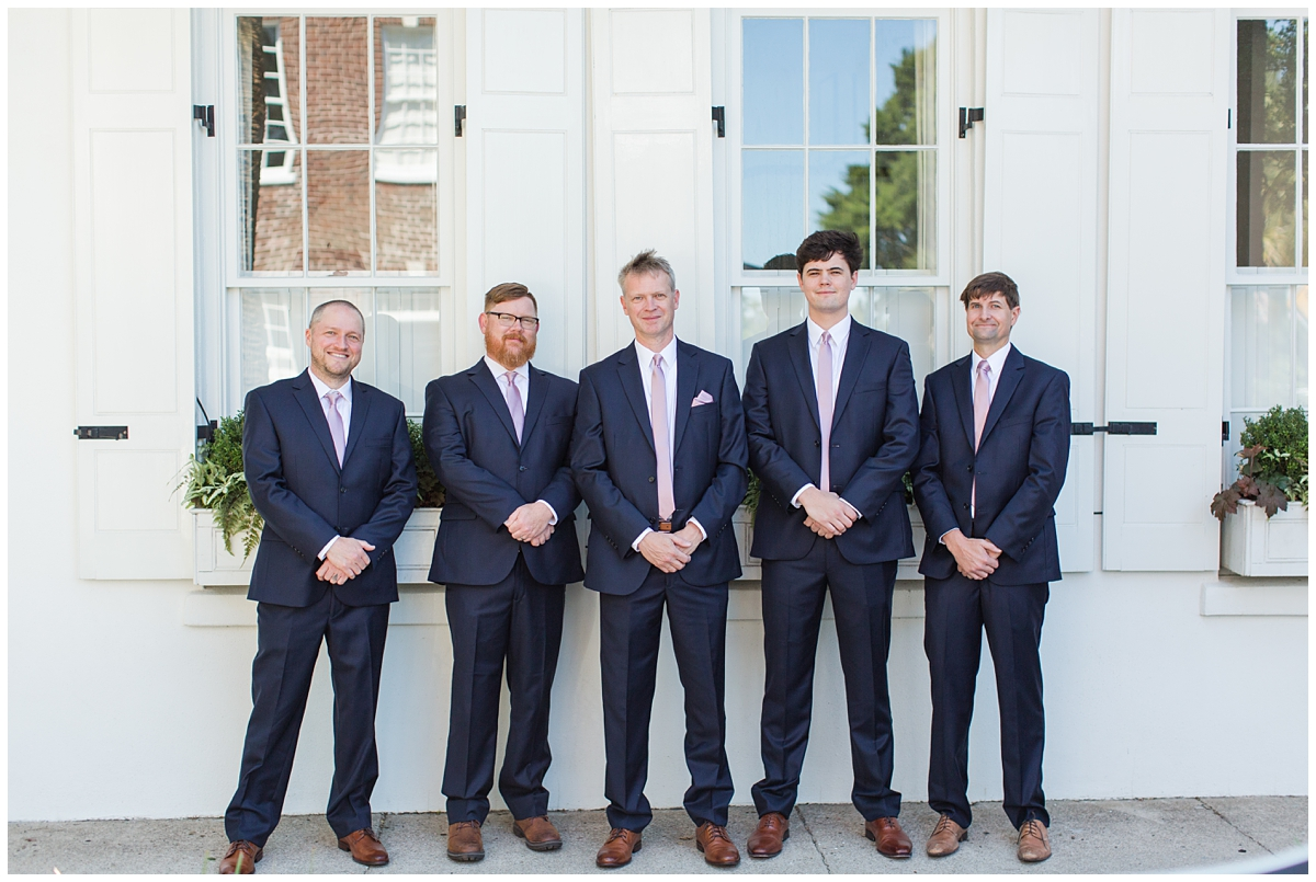 groom and groomsmen in navy suits pose outside Charleston house